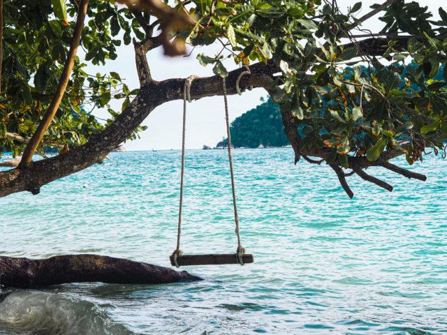 Schommel in een boom boven de zee bij Pangkor Maleisië